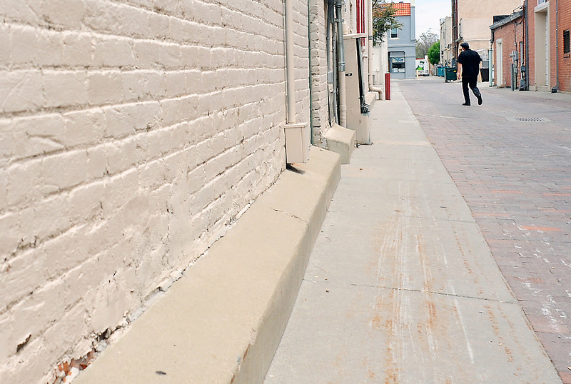 Interweave Press employee Rico Garcia carries a box of mail in the alley behind the business in the 200-block between 4th and 5th Avenues in downtown Loveland.
