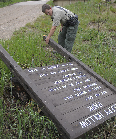 Reporter-Herald/ Chad Spangler<br /> Steve Gibson, a park ranger for Larimer County Open Space, checks out a downed sign at the entrance of Sleepy Hollow on Saturday afternoon. Along with medical and law enforcement responsibilities the rangers in Larimer Country document and repair damages to infrastructure within the parks.