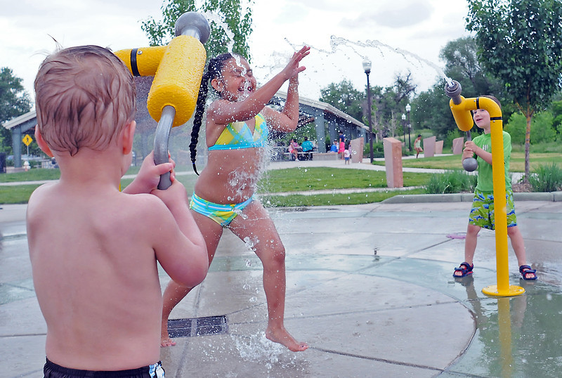 Seven-year-old Reyna Lozoya, center, has water squirted on her by Brendan Keeney, 3, left, and Brent Harris Jr., 4, while they play together Tuesday afternoon at Fairgrounds Park.