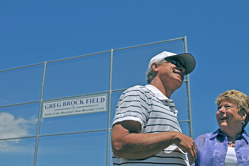 Greg Brock, left, converses with former boss and coworker, Sue Wall, right, Monday, shortly before Mountain View High School dedicated their baseball field to him.
