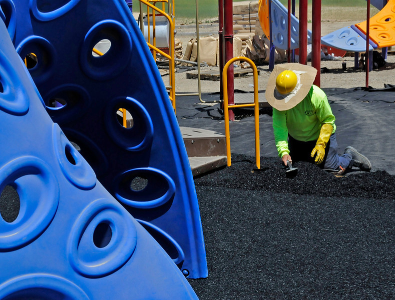 Arturo Espino puts down some rubber surfacing in one of the playgrounds at Ponderosa Elementary School.