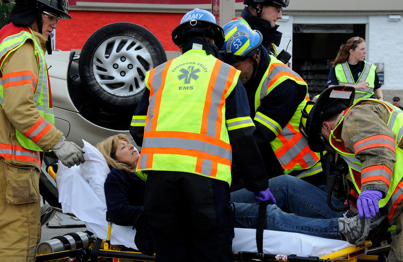 Mary Palmer is assisted by firefighers after her car flipped in an accident with another car on West Eisenhower Ave on Monday. Palmer was taken to McKee Hospital with cuts to her left arm. The cause of the accident is still under investigation.