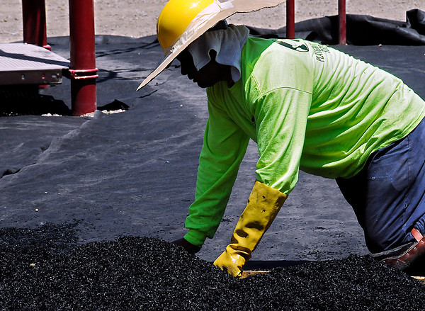 Arturo Espino puts down rubbering surfacing at the new Ponderosa Elementary School on Florance Drive. The high in Loveland on Friday reached 98 degrees.