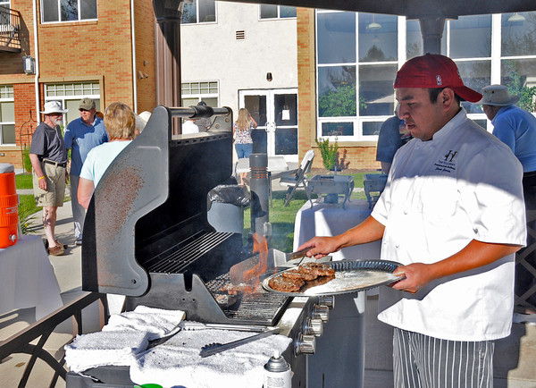 Javier Garcia runs the grill for the neighborhood block party held at the Hillcrest senior living community . Last night, Lovelander's were joined by firemen and Policemen out to encourage neighbor involvement at different block parties thrown around the city.
