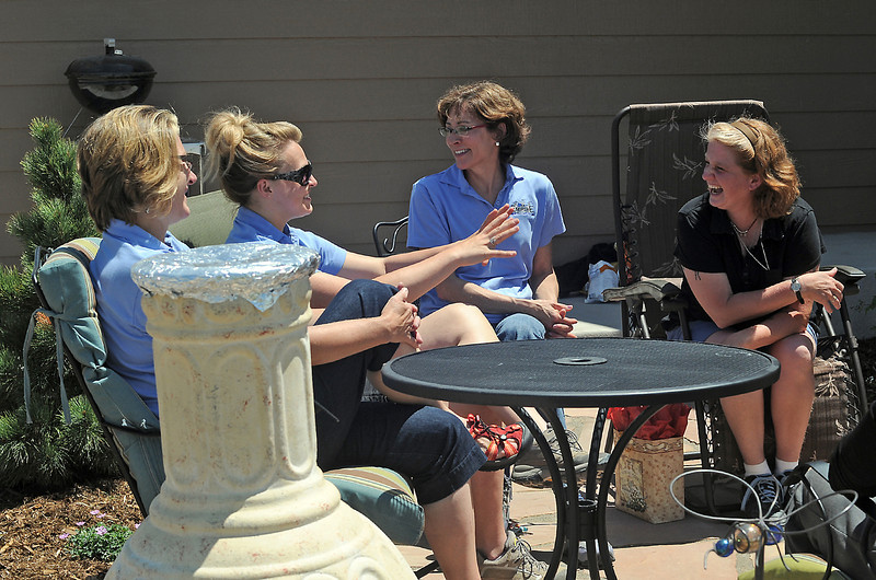Deserie Newton, right, shares a laugh on the patio in her backyard Wednesday with the Empire Landscaping employees who designed and installed the patio and landscaping of her new Habitat for Humanity home in Loveland. From left are Anne Clark, Lacey MacLennan and Sally Guthart.