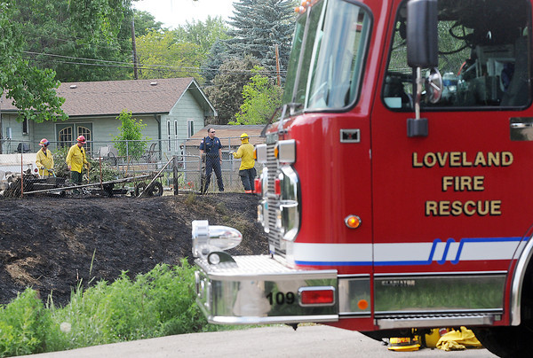 Loveland Fire and Rescue Department personnel work the scene of a grass fire Friday afternoon near Jackson Avenue and 15th Street.