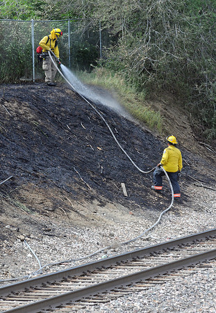 Loveland Fire and Rescue firefighters work the scene of a fire Friday afternoon west of Jackson Avenue and 15th Street along the railroad tracks.
