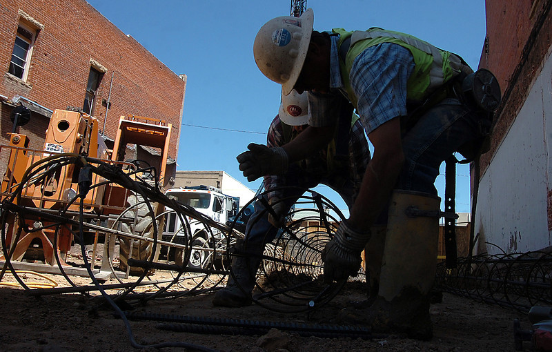 Construction workers Jason Waneka, front, and Geraldo Quezada, cut a steel cason cage Monday while working to prepare the foundation for the Rialto Bridge in downtown Loveland. Photo by Jenny Sparks