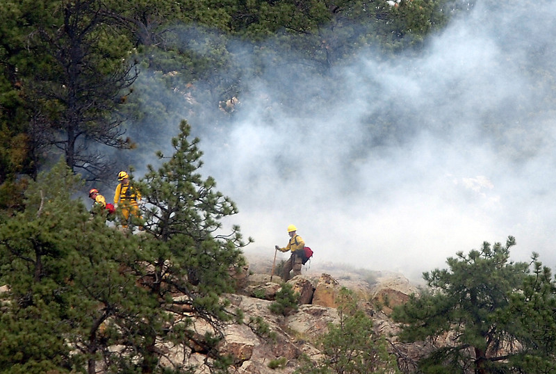 Loveland Fire and Rescue firefighters work to contain a fire Wednesday near Larimer County Road 18E between Flatiron Reservoir and Pinewood Reservoir west of Loveland. Crews dug a scratchline around the approximately 50 foot by 50 foot fire and said if the wind doesn't pick up the fire won't threaten any homes. Photo by Jenny Sparks