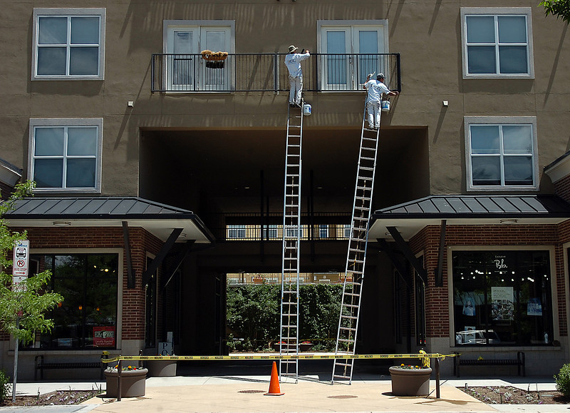 Juan Gomez, left, and Francisco Cazares paint the railing of a third floor balcony Thursday at Lincoln Place in downtown Loveland.