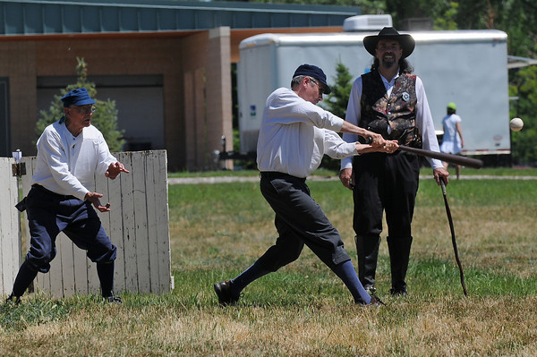 Tim Katers, middle, takes a swing at a pitch while catcher, or behind, Herb Meeker, left, and umpire Traveller Tinney look on during a Vintage Base Ball game on Sunday at Fairgrounds Park.