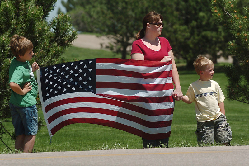 Loveland residents Cameron Hutson, 9, left, Jenny Hutson and Connor Hutson, 5, stand together outside Resthaven Cemetary holding an American flag as the funeral procession for Chief Warrant Officer Kenneth White passes by them.