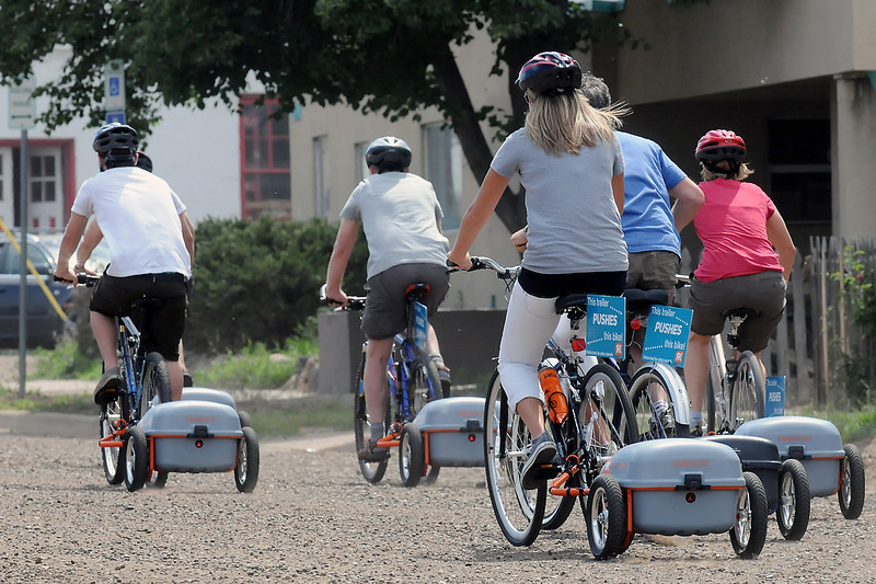 A group of bicyclists rides in downtown Fort Collins on Friday afternoon on bikes outfitted with the Ridekick device which can provide a push via an electric motor in the trailer.