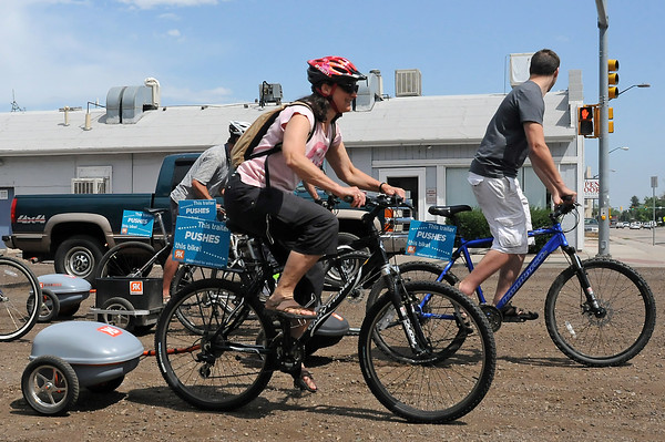 Ridekick International co-owner Dee Wanger, front, rides with others in downtown Fort Collins on Friday using power trailers which assist the riders in propelling the bikes.