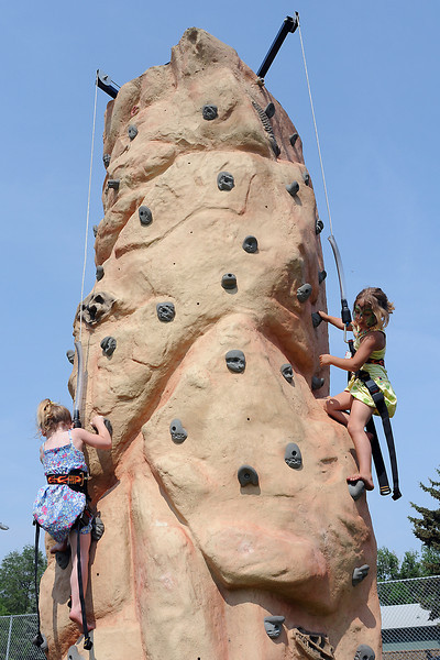 Berthoud resident Rhyan Morris, 3, left, and Olivia Miller, 5, of Parker scramble up a climbing wall Saturday afternoon during the Berthoud Day celebration at Berthoud Park.