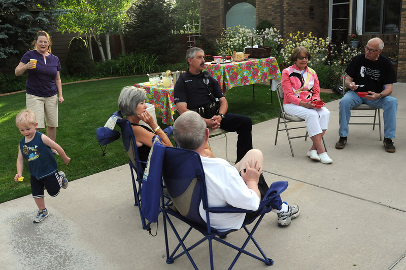 Joyce Honea, back left, looks on while her two-year-old grandson Timothy Baker dashes around while playing during a Community Night Out event on Wednesday evening at a home in the 900-block of Logan Court. Loveland Police Officer Jim Betrus, middle, chatted with residents of the neighborhood at the gathering and answered questions during his visit.