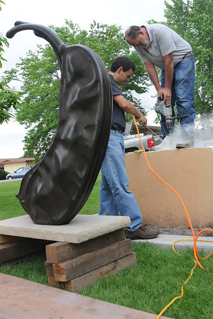 """Fort Collins-based artist Tony Hochstetler, left, blows dust out of a hole being drilled by Greg Hoff during the installation of Hochstetler's bronze sculpture """"Bean Pods, Garden Size"""" on Thursday afternoon at Benson Park Sculpture Garden in Loveland. The official dedication for the piece will be at 11 a.m. on July 9."""