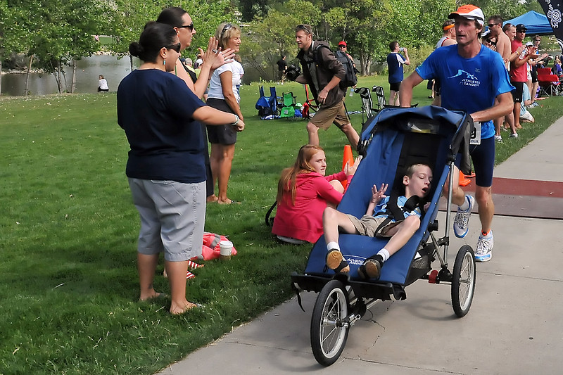 Fort Collins resident Dennis Vanderheiden, right, pushes a cart that James Waechter, 10, is riding in while they compete together in the Lake To Lake Triathlon on Saturday at North Lake Park as part of the Athletes in Tandem program.