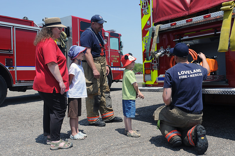 Loveland Fire and Rescue firefighters Matt DeDecker, right, and Paul Brown, back, explain some of the features of a fire truck to Loveland residents, front from left, Julie Mowen, Caris Mowen, 7, and Seth Mowen, 4, during a 100th anniversary celebration for the department Saturday at the fire training facility.
