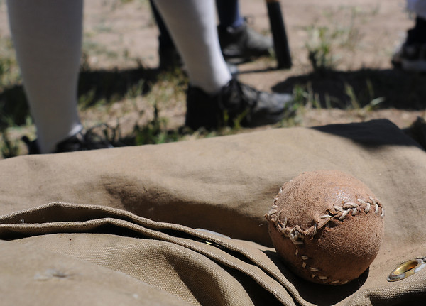 A hand-stitched base ball rests on a canvas bag while players await their turn at bat during a Vintage Base Ball game on Sunday at Fairgrouds Park.