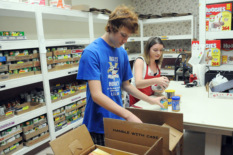 House of Neighborly Services volunteer Luke Gates, 14, left, and food room assistant Joanna Perciante sort Thursday through boxes of food that was donated as part of the Have a Heart food drive.