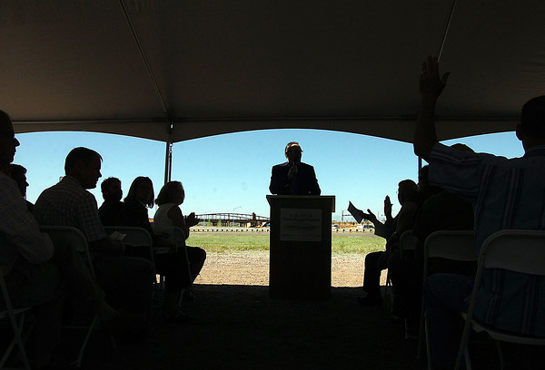 With the new interchange in the background, Dave Klockeman, City Engineer for the City of Loveland, encourages folks to clap and recognize those involved in the I-25/U.S. 34 Interchange project Tuesday morning during a ribbon cutting ceremony in Loveland. Photo by Jenny Sparks