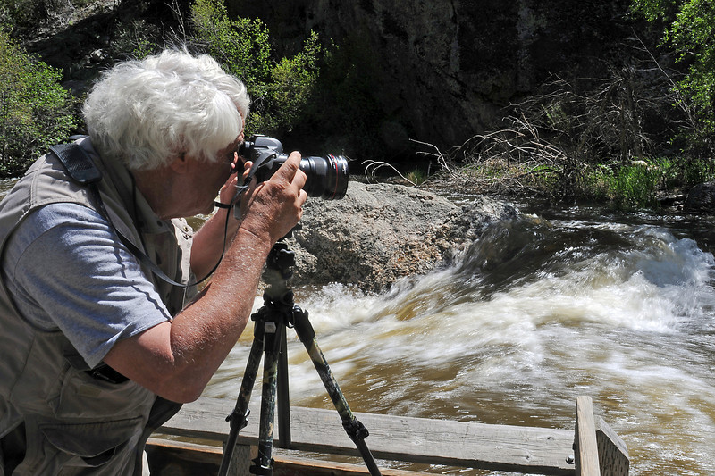 Loveland resident Gary Batha photographs the Big Thompson River as it rushes past a fishing ramp along the river east of Estes Park on Tuesday afternoon. Batha said he had recently photographed at the same spot and that the water level was noticeably higher than the last time he was there.