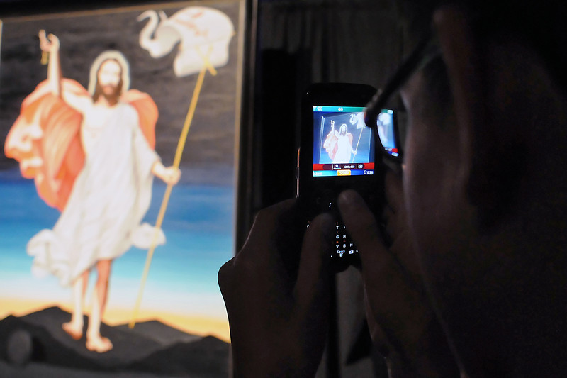 Loveland, Colo. resident Ethan Rosier, 13, uses his cell phone to take a picture of a painting of Jesus Christ by artist Enrique Chagoya that was unveiled during a service at Resurrection Fellowship, 6502 E. Crossroads Blvd., in Loveland on June 18, 2011.