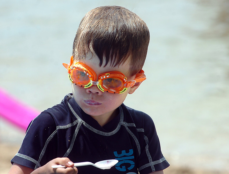 Stiil sporting his goggles after splashing around in the water at the swim beach, Isaac Baumeister of Loveland, 5, munches some yogurt and fruit Wednesday at North Lake Park in Loveland. Photo by Jenny Sparks
