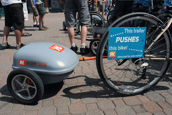 The Ridekick device consists of a trailer containing an electrick motot that is pulled behind the bicycle and can be used to provide assistance to the rider by pushing the bike along.