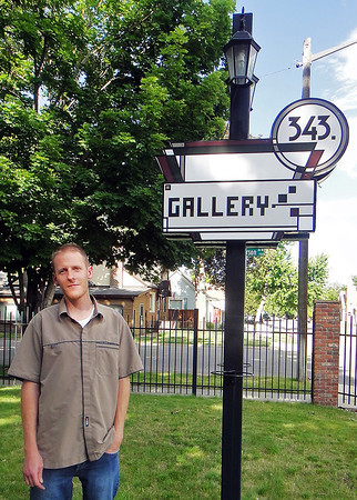Peter Dougherty, owner of 343 Gallery, poses Thursday June 6, 2013 for a photo showing off the lamp post he made in front of the gallery.