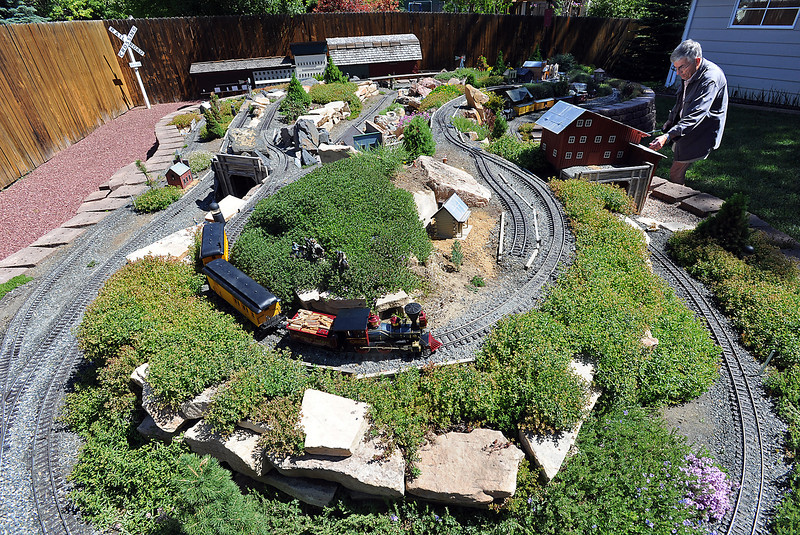 Bob Ferrero flips a switch Thursday June 6, 2013 to make another train go on the tracks of his garden railroad in his Loveland backyard. His is one that will folks can see during the Garden Railroaders tour this Saturday.