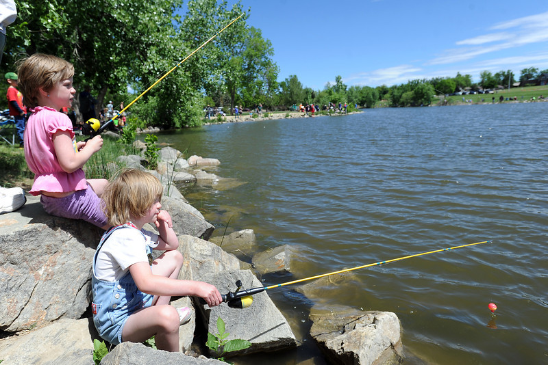 Seven-year-old Renata Means, left, and her twin sister Cassidy Means fish together during the Loveland Fishing Derby on Saturday, June 1, 2013 at North Lake Park.