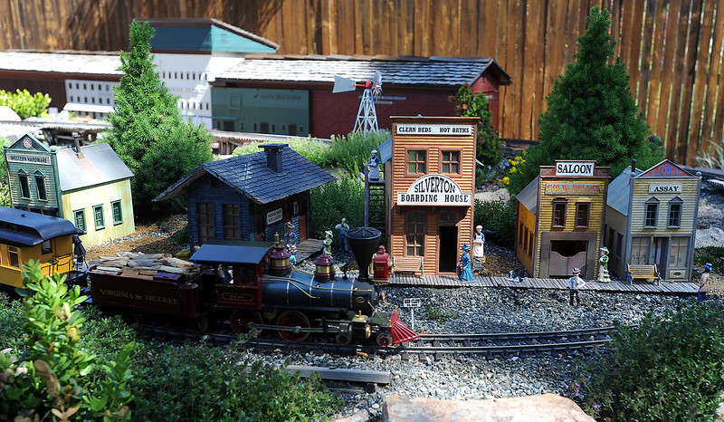 Figures and storefronts decorate Bob Ferrero's garden railroad Thurdsay June 6, 2013 as his passenger train goes by in his Loveland backyard.