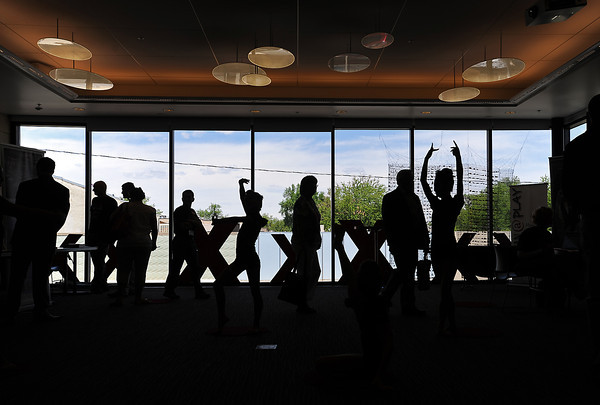 Dancers from The Studio are silhouetted as they strike poses while people walk around Friday, May 31, 2013 during an event in the Devereaux Room at the Rialto Theater Center in downtown Loveland. The Devereaux and Hach rooms on the second floor were intended to be the newest venue spaces in town for a variety of events when the space opened about a year ago.