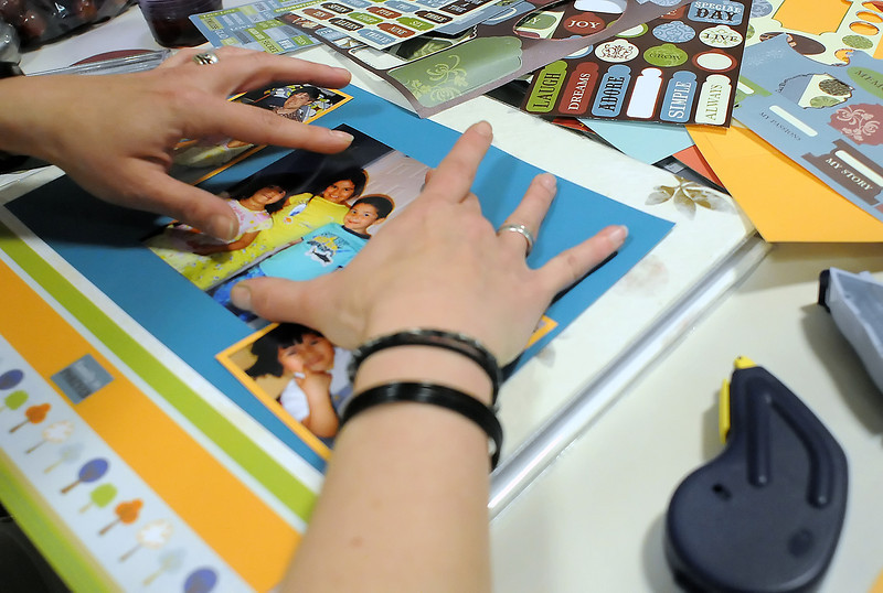 Jill Hawley lays out a scrapbook page with pictures of her family during the Crop for a Cure fundraiser for cancer research Saturday at Centennial Elementary School.
