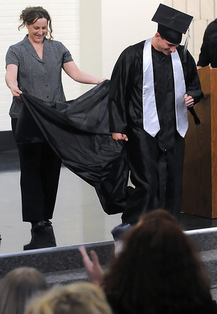 Ferguson High School science teacher Cathy Beach holds up a bustle that she pinned onto student Kobi Vargas' graduation gown as a bustle during the school's third quarter graduation ceremony on Thursday, March 11, 2010.