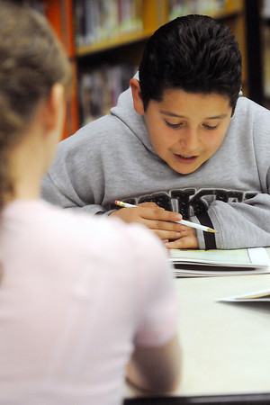 Conrad Ball Middle School eighth grader MaKenzie Ross, 13, left, assists sixth grader Salvador Lopez, 12, as he reads a book aloud during the Learning Together program Tuesday in the school's library. The program pairs a sixth grade student with an eighth grader who then becomes their reading tutor.