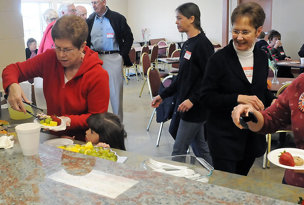 Penny Farias, left, and her granddaughter Ashlyn Welch, 3, get some snacks during an event for Loveland Community Kitchen volunteers Thursday at the facility's new location at 437 N. Garfield Ave.