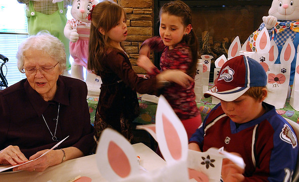 Helen McDill, left, and Kyle Moore, right, finish making easter bunny baskets while Maddie Sabin, center left, and Lily Smith, center right, rush to the tables collecting them. The Giving to Others group from Big Thompson Elementary joined up with residents of Sterling House on Sunday to complete the craft.