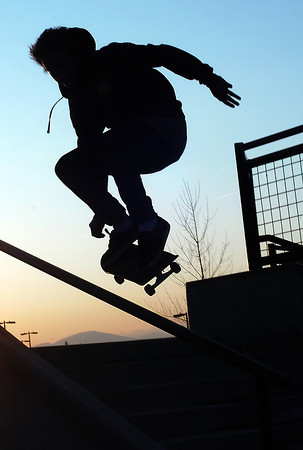 Loveland resident Donandrew Romero, 17, is silhouetted against the setting sun to the west as he ollies over the handrail to some steps at the Loveland Sports Park while skateboarding Thursday evening.