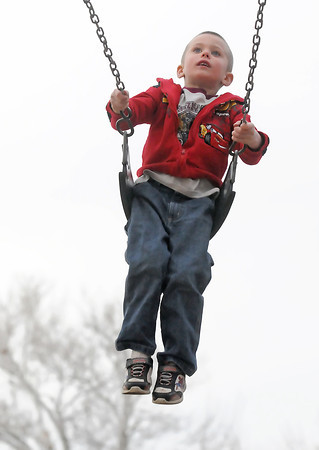 Five-year-old Dylan Gutknecht peers around from the top of the swingset while playing at Dwayne Webster Memorial Park with his little brother and grandmother on Saturday.