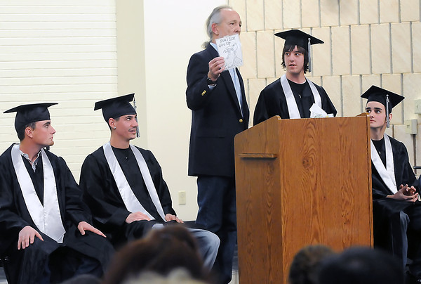 """Ferguson High School math teacher Chris Carstensen, center, holds up a drawing with the phrase """"Don't Ever Give Up"""" as he presents it to Tyler Dechant during the school's third quarter graduation on Thursday. Seated from left are graduates Taylor Zweigle, Kobi Vargas and Jack Ross."""