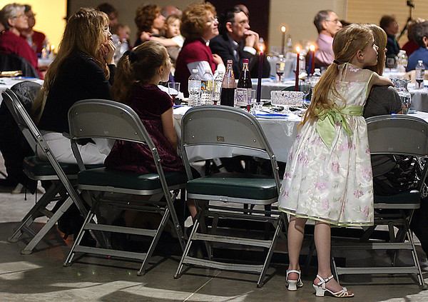 """Kiley Burlando, age 7, hugs her mom while watching a clip from the movie """"Road to Eldorado"""".  The movie was part of the educational presentation put on by Y'shua and Company, Sunday, in an effort to better understand Hebrew tradtion."""