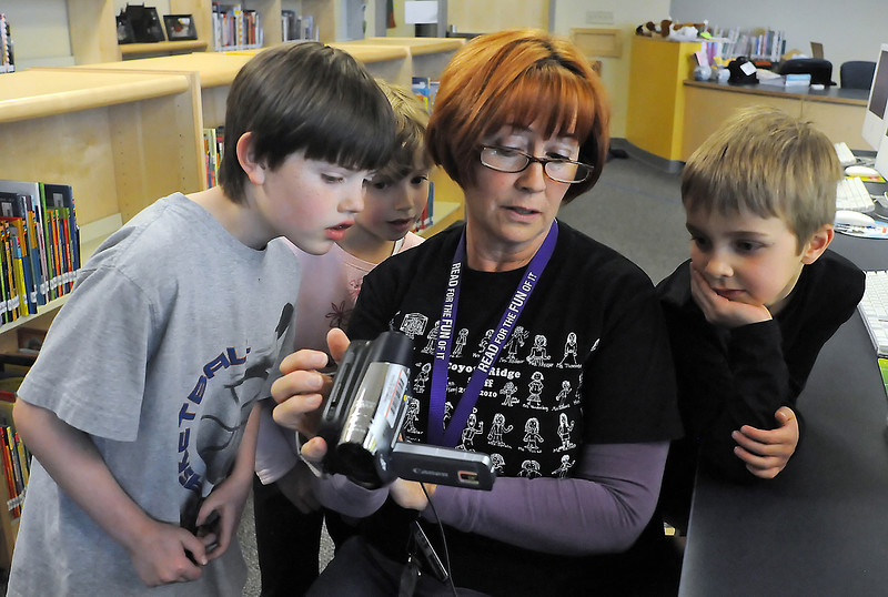 "Coyote Ridge Elementary School librarian Nancy Milliken reviews a television commercial she videotaped of second graders Rider Anderson, 8, left, Caitlin Flynn, 7, and Ethan Hansen, 7, as part of a class project on simulating an international market. The youngsters' business was called ""Metal Souvenirs"" and featured items like Eiffel Tower replicas since the market is supposed to be in Paris, France."
