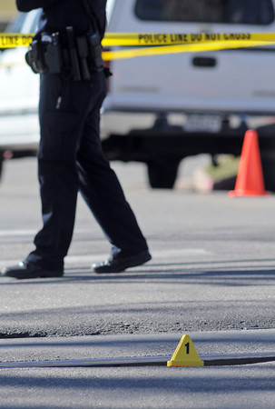 A police officer walks past an evidence marker by the train tracks at the scene of a fatal train versus pedestrian accident at Old Main Drive and Mason Street on the Colorado State University campus in Fort Collins on Friday, March 12, 2010.