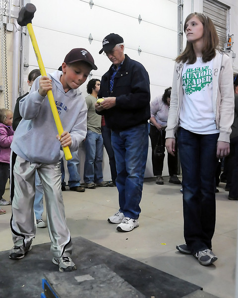 Windsor resident Camden Carlson, 10, tries to ring the bell as he takes a swing at the North 40 4-H Club's high striker booth being run by Madeline Burbach, right, on Saturday during the 4-H Carnival and Crafts Show at The Ranch.