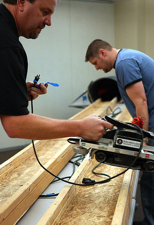 Jason Kingery, right, readjusts the lanes crafted for The Northern Colorado's Homebuilders Association's Mar 6 belt-sander races, while Jim Iversen lends a hand.