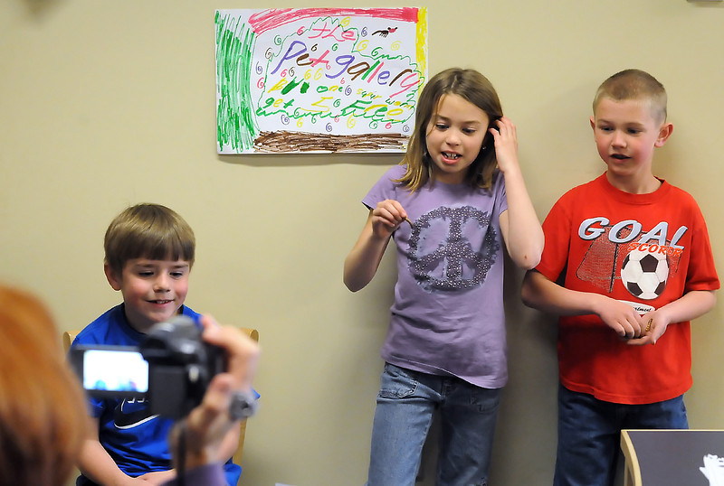 "Coyote Ridge Elementary School second graders David Strasbaugh, 8, back left, Sammie Gordon, 8, and Blaine Tucker, 8, are videotaped by librarian Nancy Milliken as they produce a television commercial for their pet store business called ""The Pet Gallery."""
