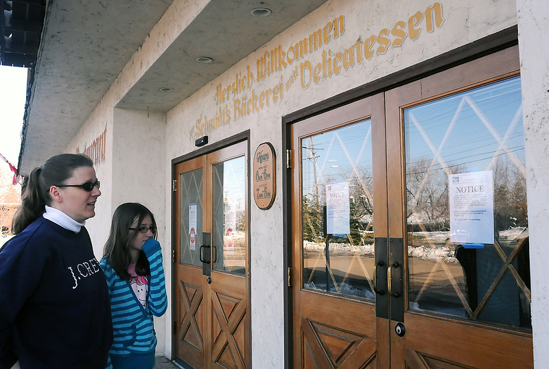 Cheryl Kouns, left, and her daughter, Faith Kouns, 11, read a sign posted Wednesday on the front door of Schmidt's Bakery and Delicatessen, 808 SW 14th St., annoucing the business' closure by the City of Loveland due to failure to remit sales taxes.